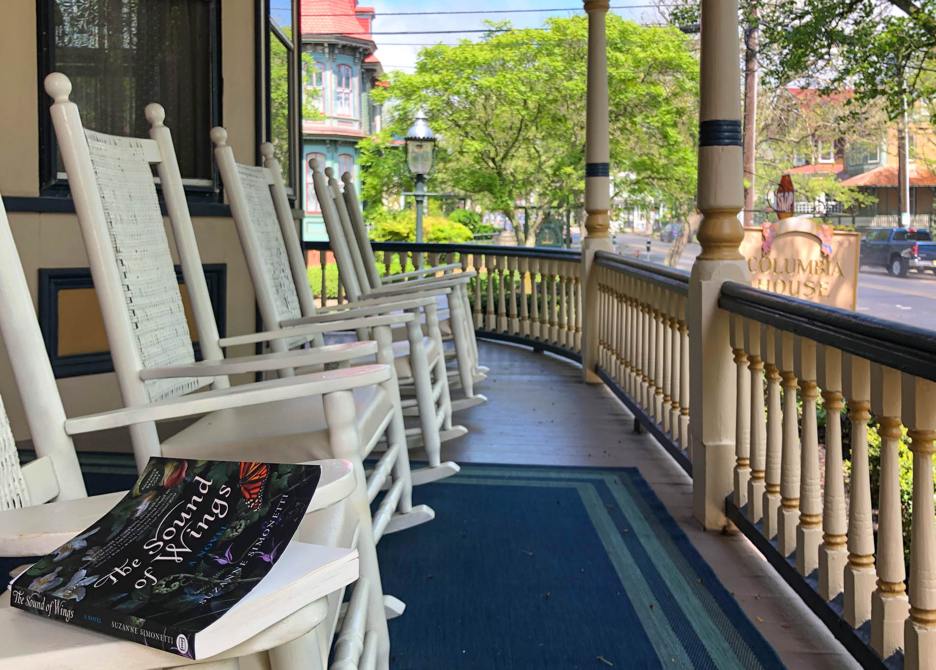 sitting on the Columbia House porch with the book The Sound Of Wings