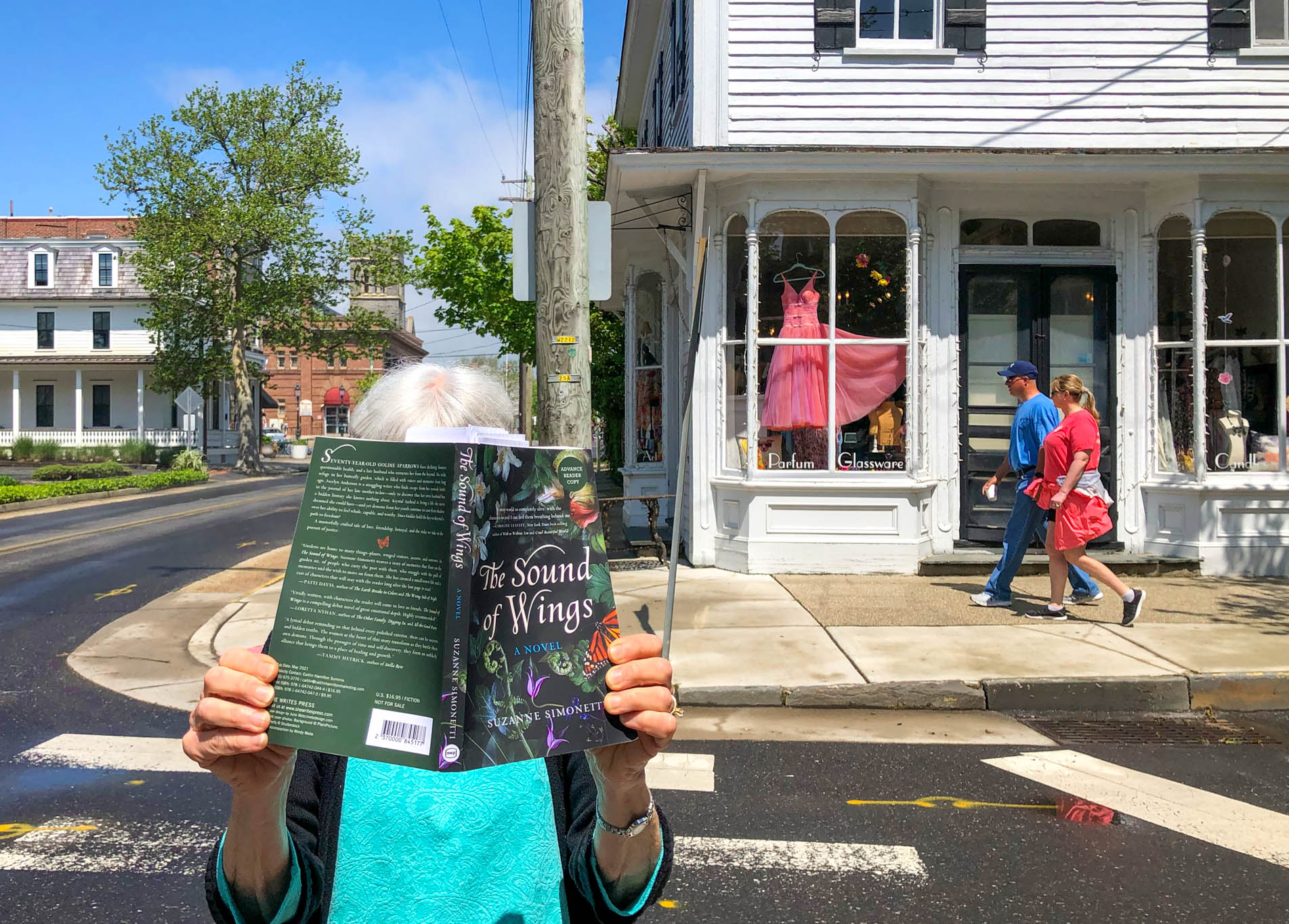 A lady on the corner of Ocean St and Hughes St with the book The Sound Of Wings