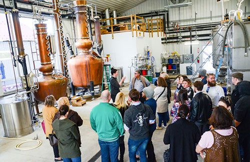 Tour group in front of copper stills at Nauti Spirits