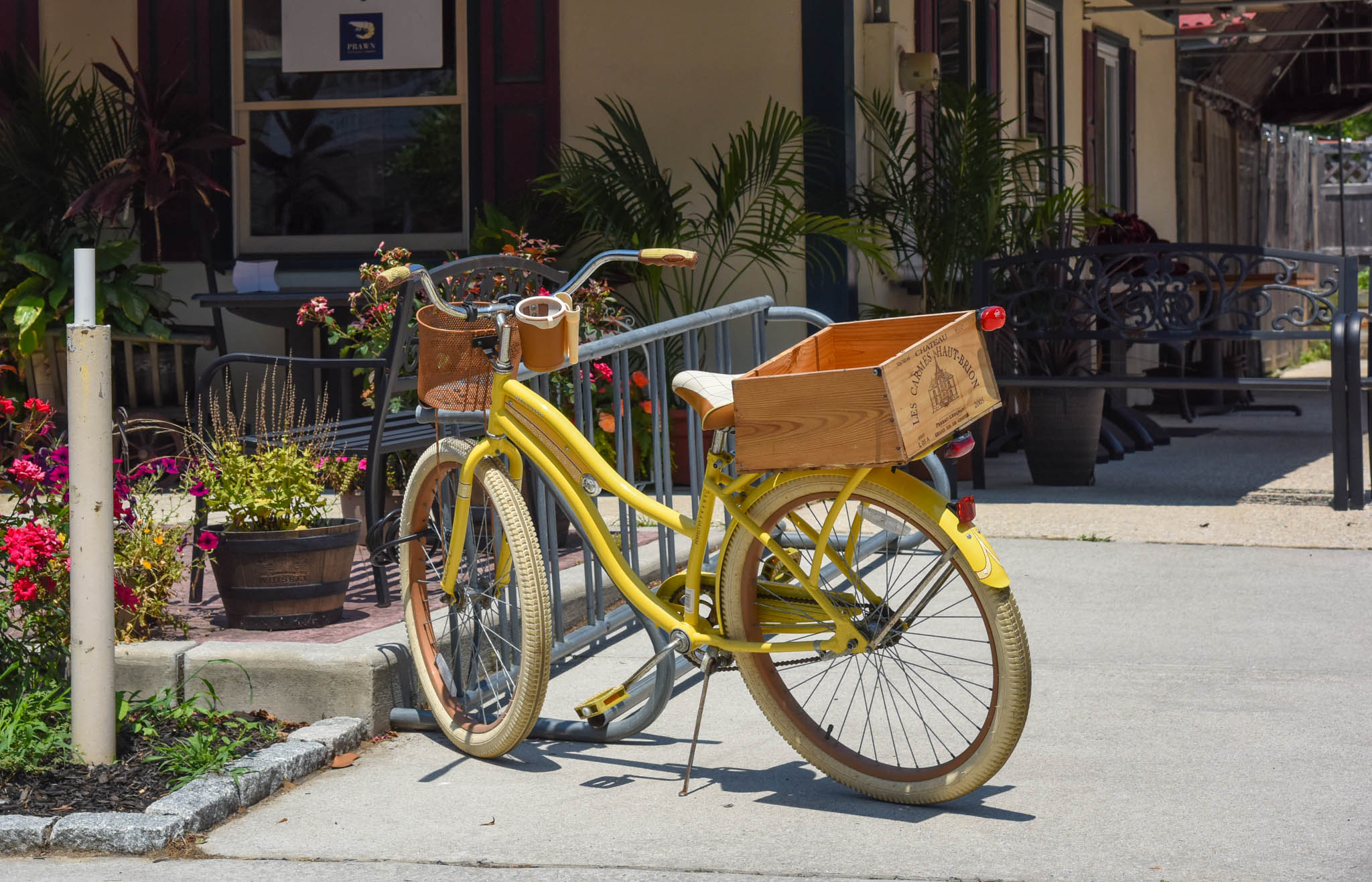 Yellow bicycle with wooden basket parked outside of a takeout restaurant