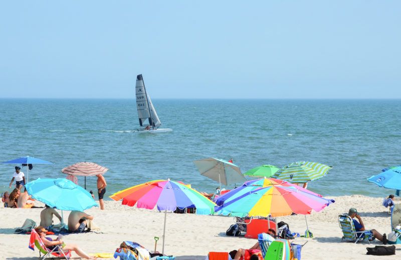 Sailboat off of Howard Beach, colorful beach umbrellas in the foreground