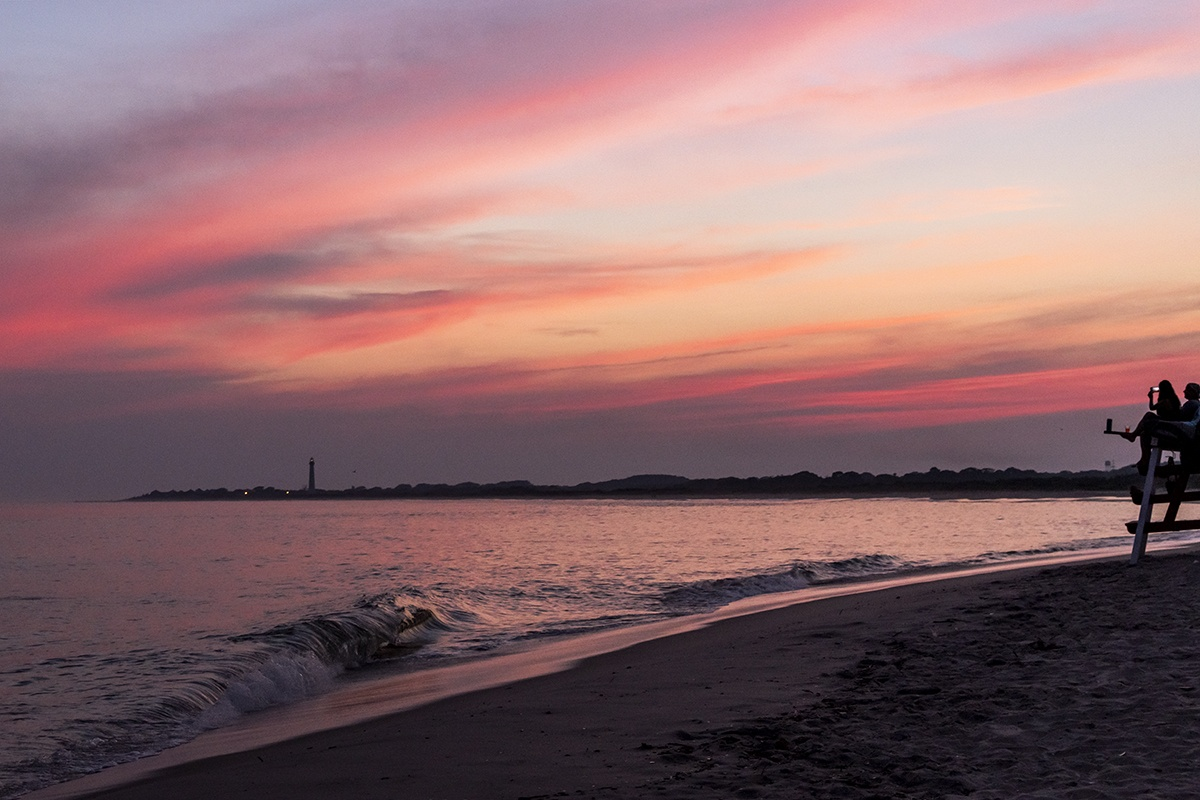 Pink skies after sunset at the beach with waves crashing on the sand