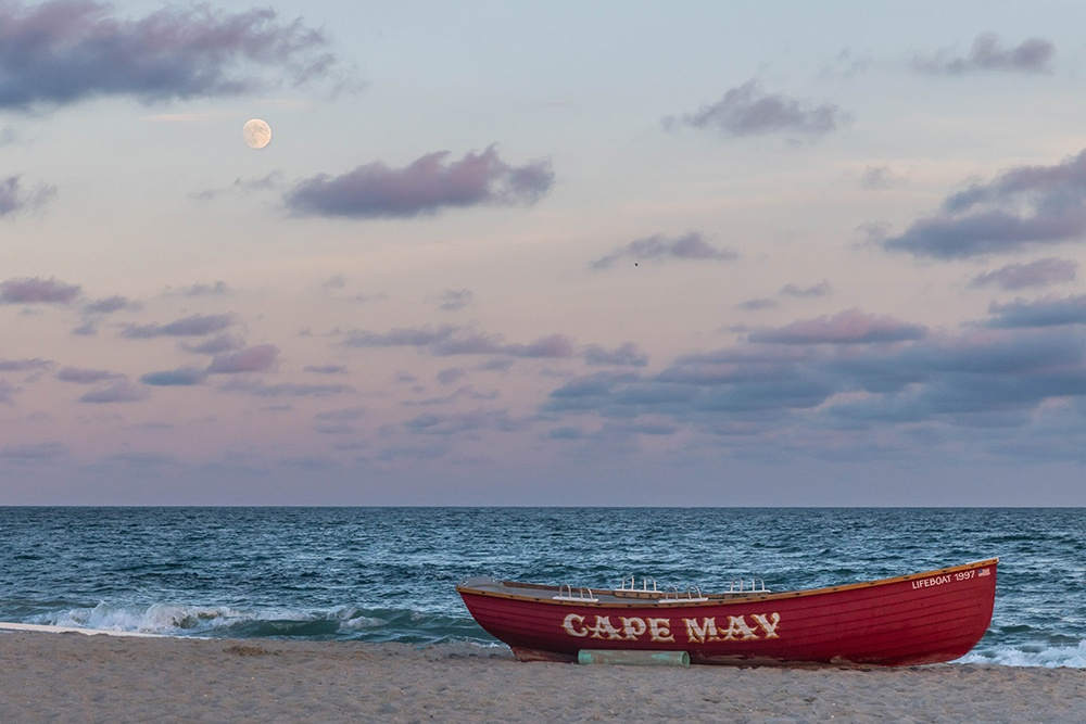 Moon rising over the ocean, beach, and Cape May lifeguard boat.