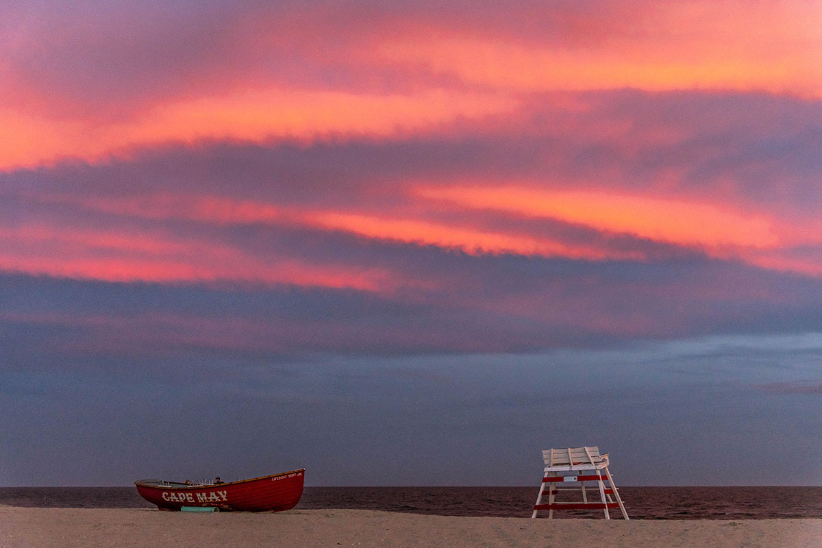 "Pink clouds in the sky with a lifeguard stand and ""Cape may"" lifeguard boat on the beach"