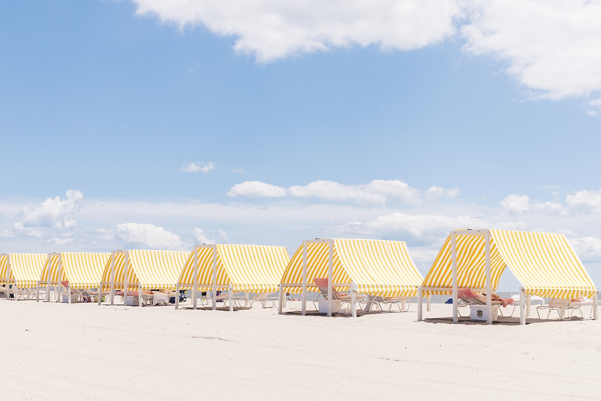 Congress Hall yellow and white beach cabanas on the beach with a blue sky