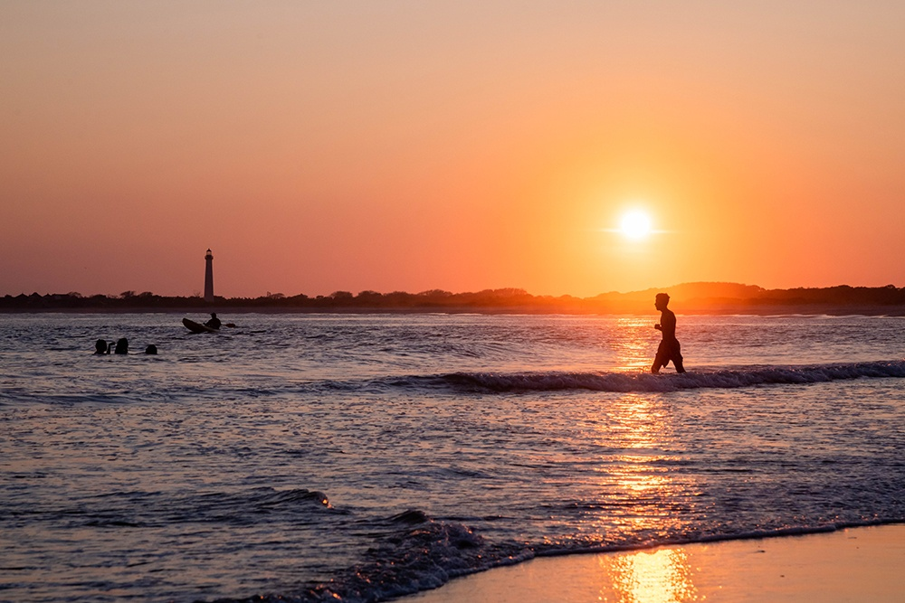 A person walking back into the ocean at sunset
