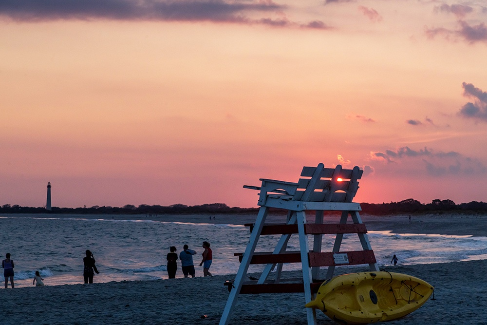 Sun setting behind a lifeguard stand while people stand by the ocean