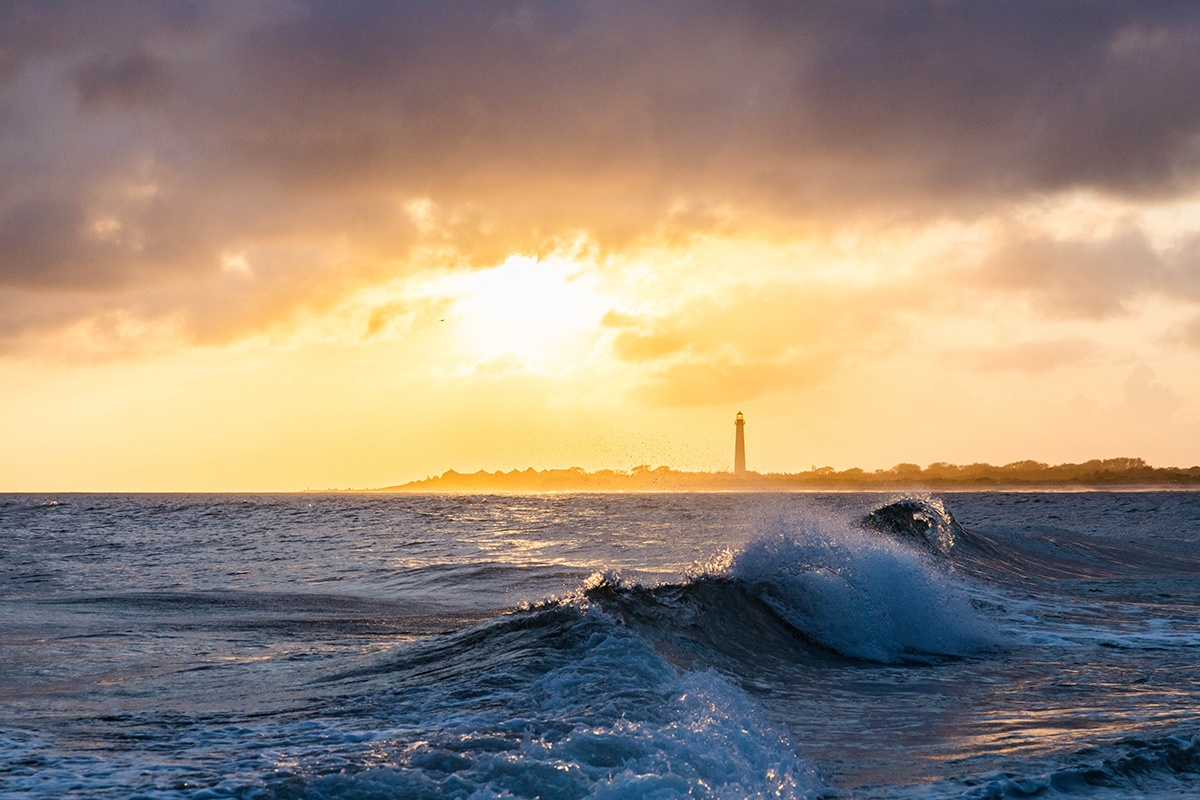 Sunset with waves crashing and clouds in the sky with the Cape May Lighthouse in the distance