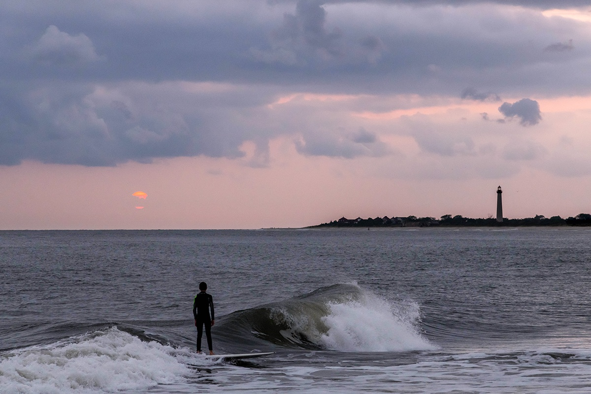 Surfer at sunset with the Cape May lighthouse in the distance