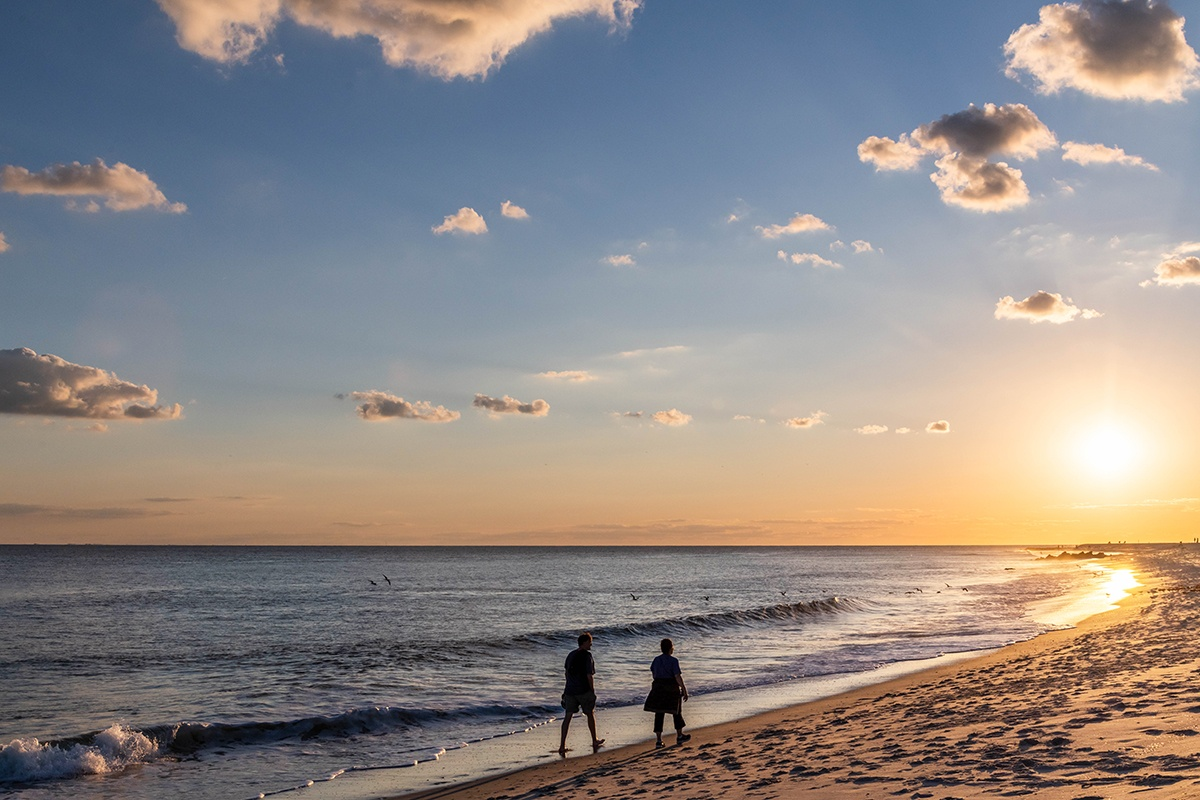 Two people walking on the beach by the ocean at sunset with puffy clouds in the sky