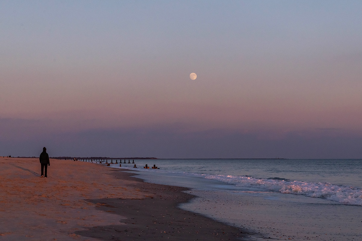 Full moon rising over the ocean with a person walking on the beach
