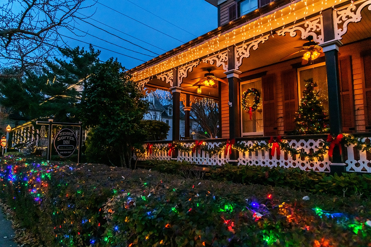 Christmas lights and decorations on a porch of a Victorian style house
