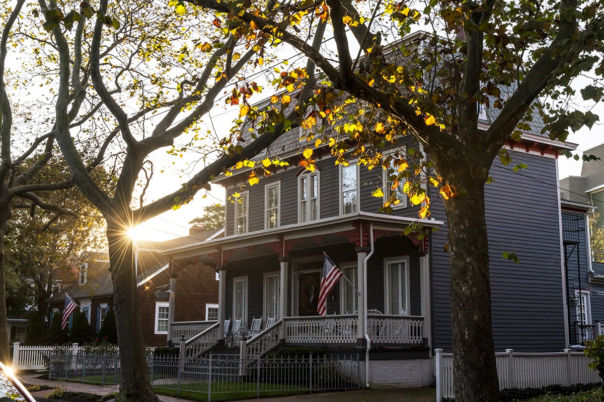 Sun setting behind trees with fall leaves and a Victorian house
