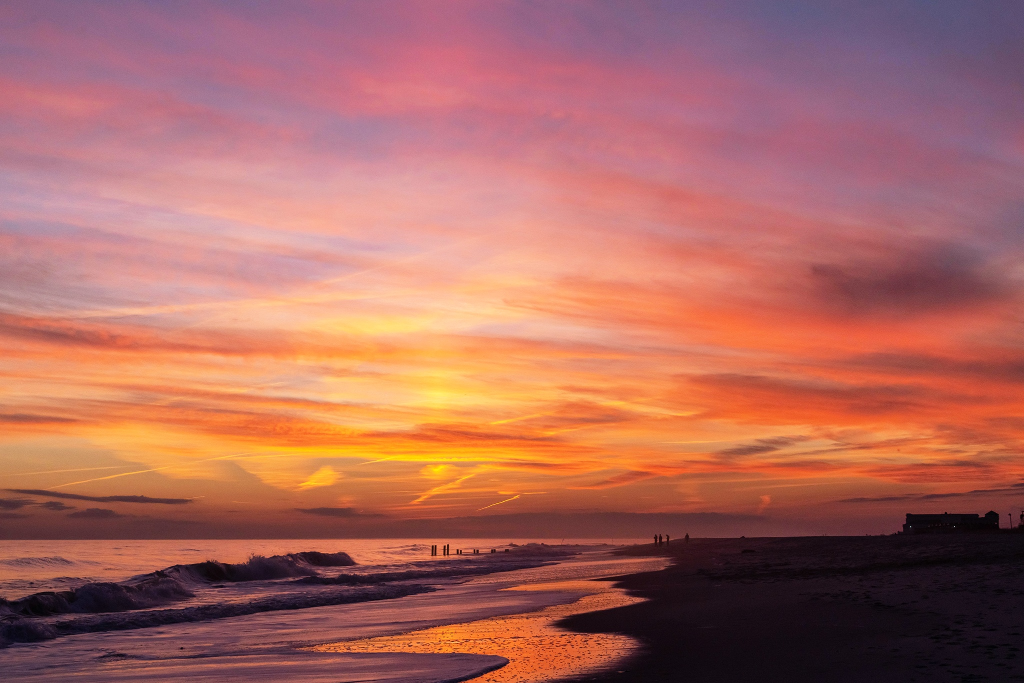 Pink, blue, orange, and yellow colors in the sky after sunset at the beach