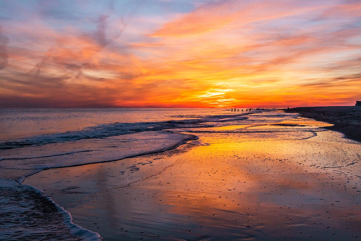 Pink, orange, and red clouds in the sky at sunset reflected in the sand