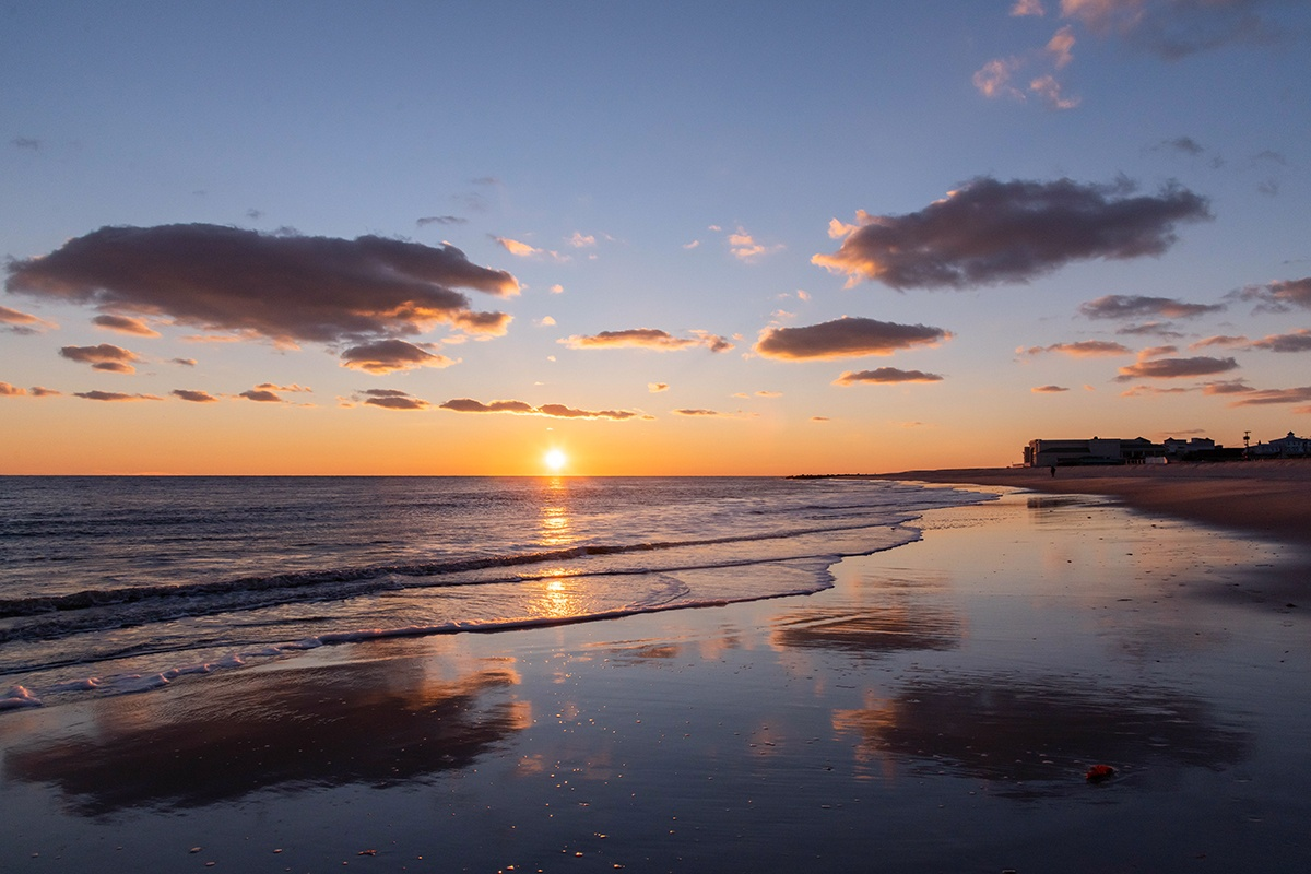 Sunset at the beach with clouds reflected in the shoreline