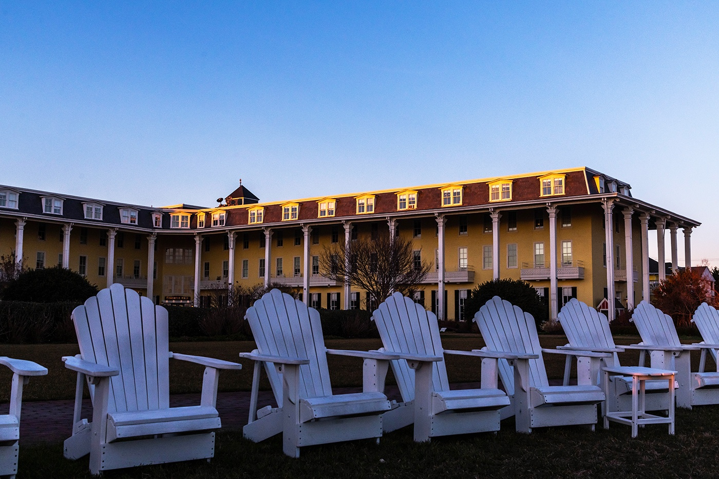 Empty white chairs on the front lawn at Congress Hall with sunlight from sunset hitting the roof