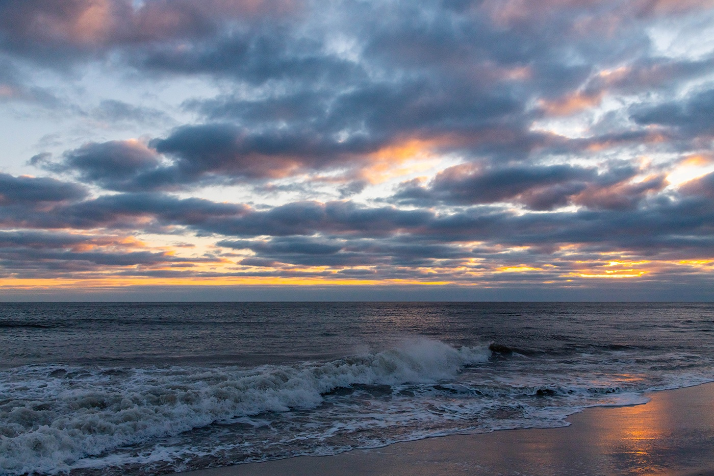 Waves crashing at sunset with clouds in the sky