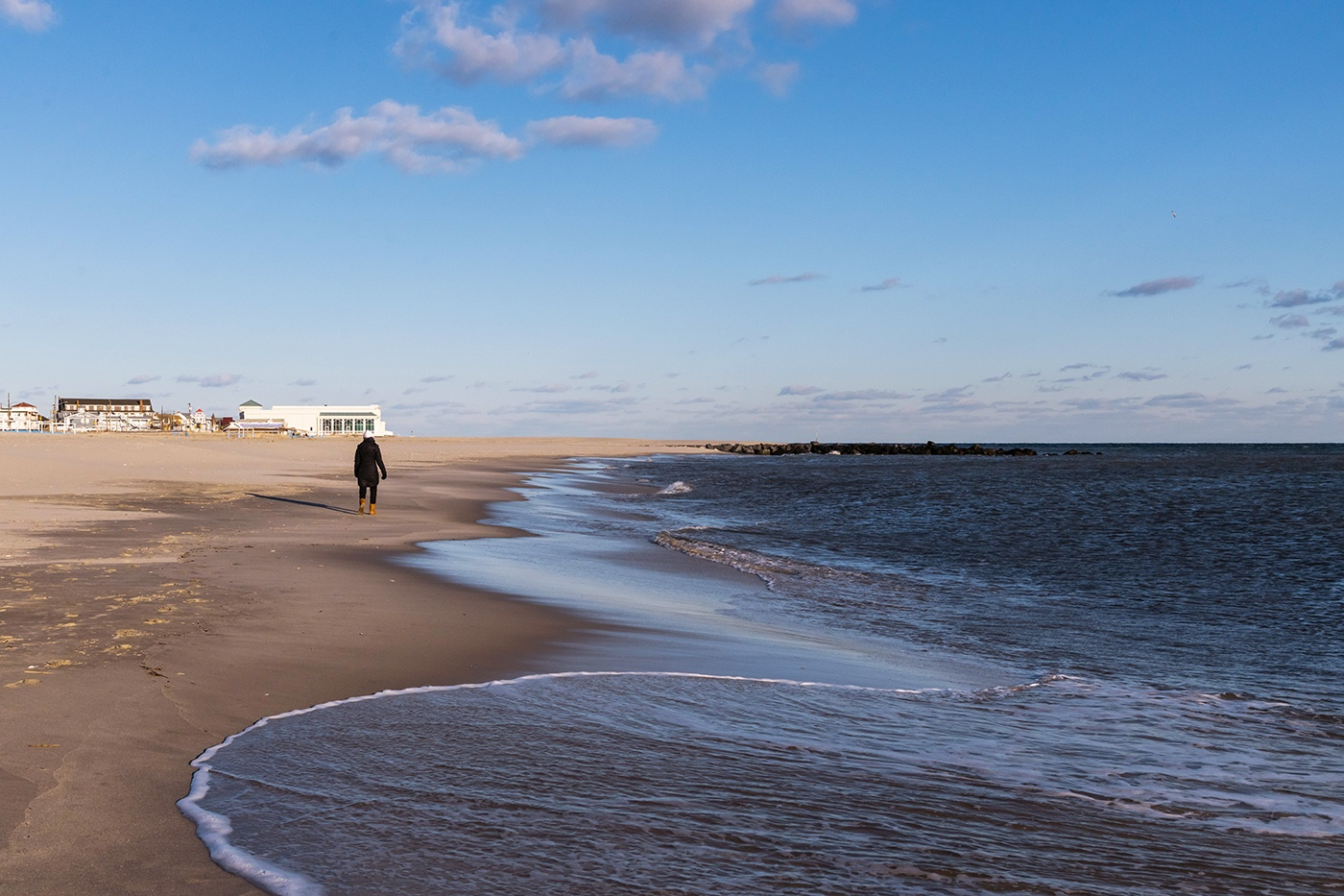 A person walking on the beach by the ocean in the winter on a bright blue sunny day