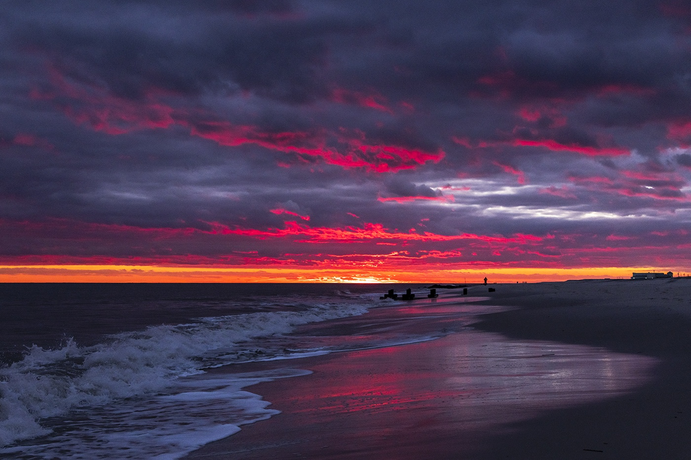 Bright pink colors in the clouds at sunset on a cloudy day with waves crashing
