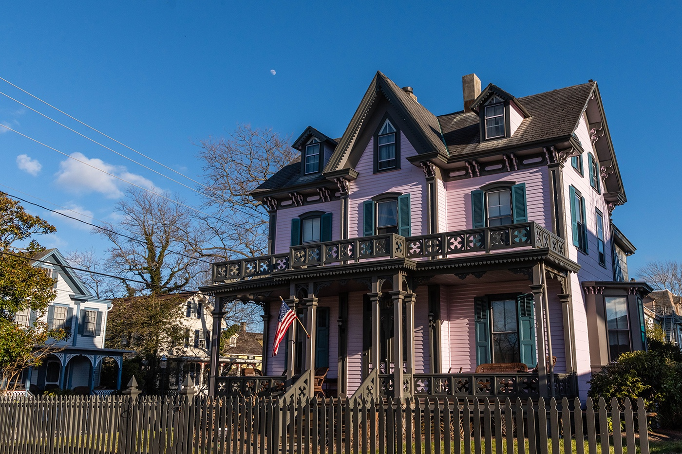 A pink and teal Victorian house on a sunny winter day with a clear blue sky