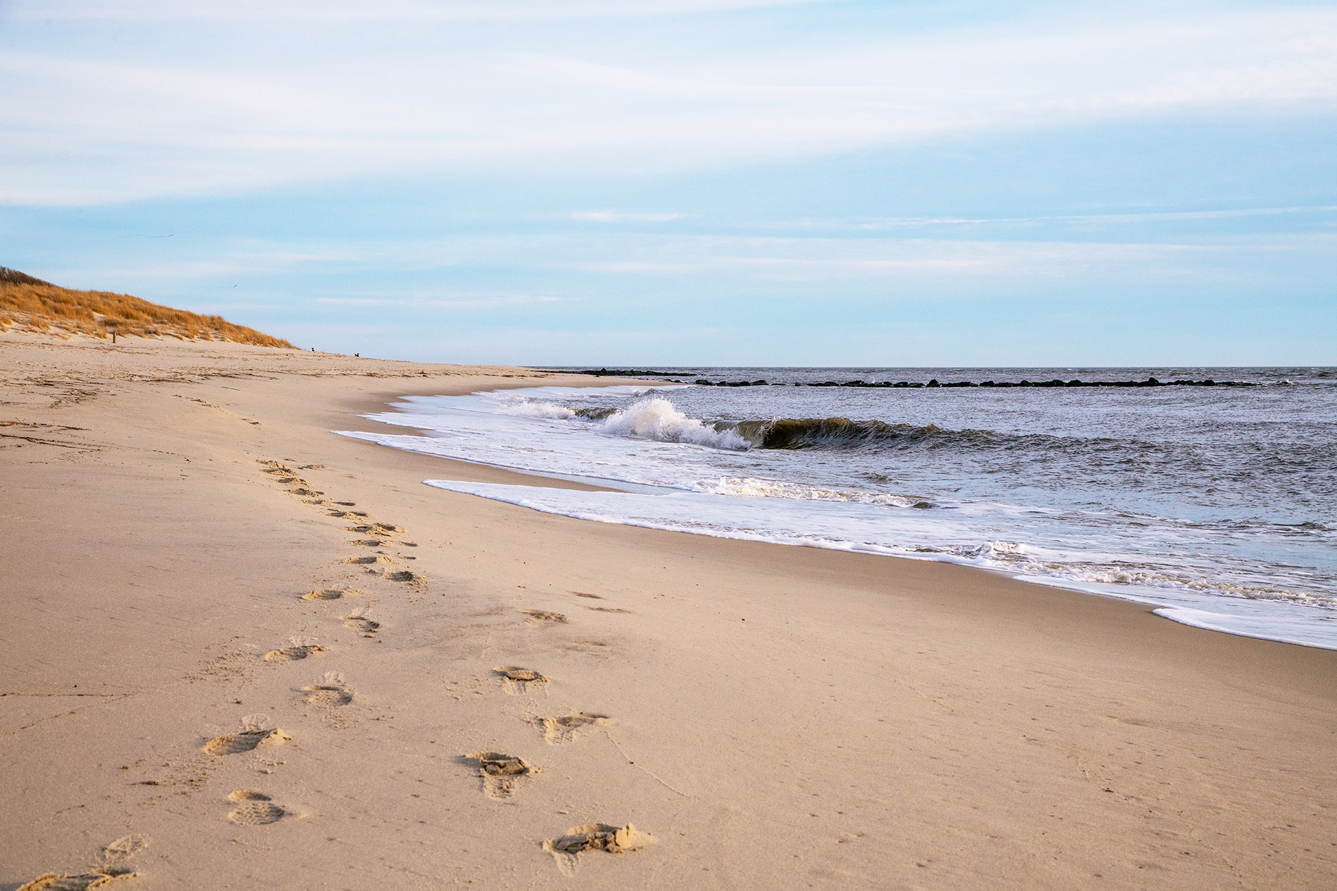 Two pairs of footprints in the sand as a wave crashes on the shore on an overcast day