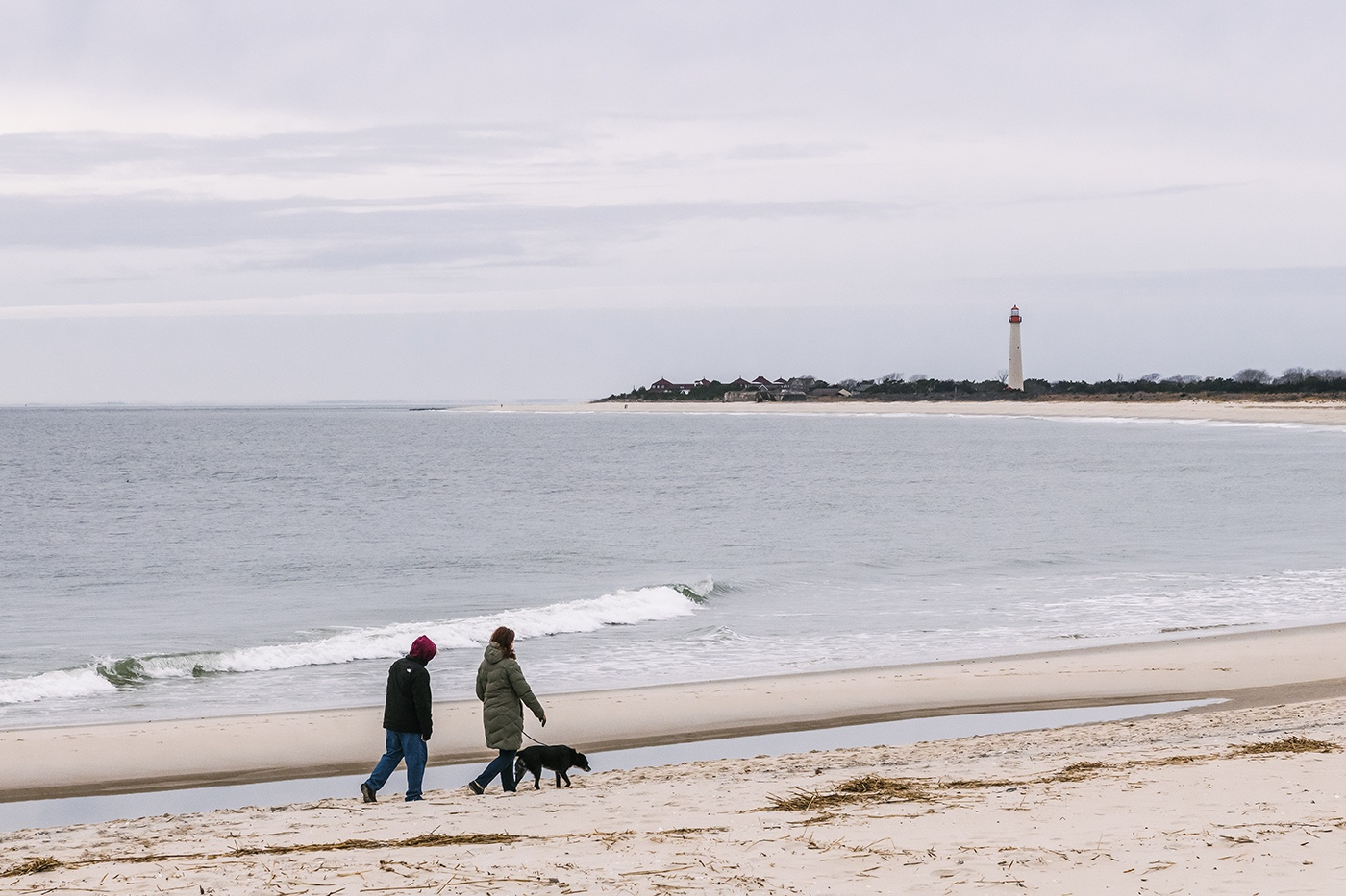 Two people walking with their dog on the beach on a cloudy day with the Cape May Lighthouse in the distance.