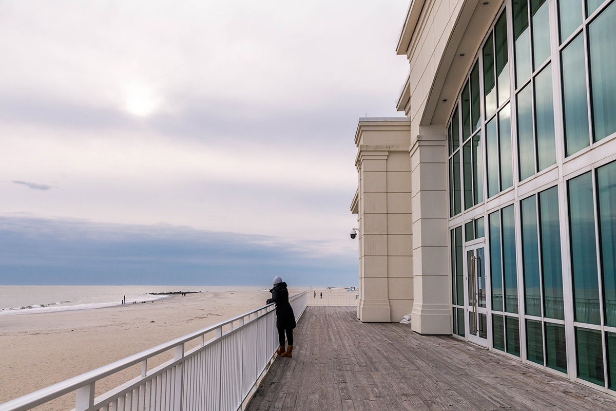 A person looking at the clouds and the beach on the deck at Convention Hall
