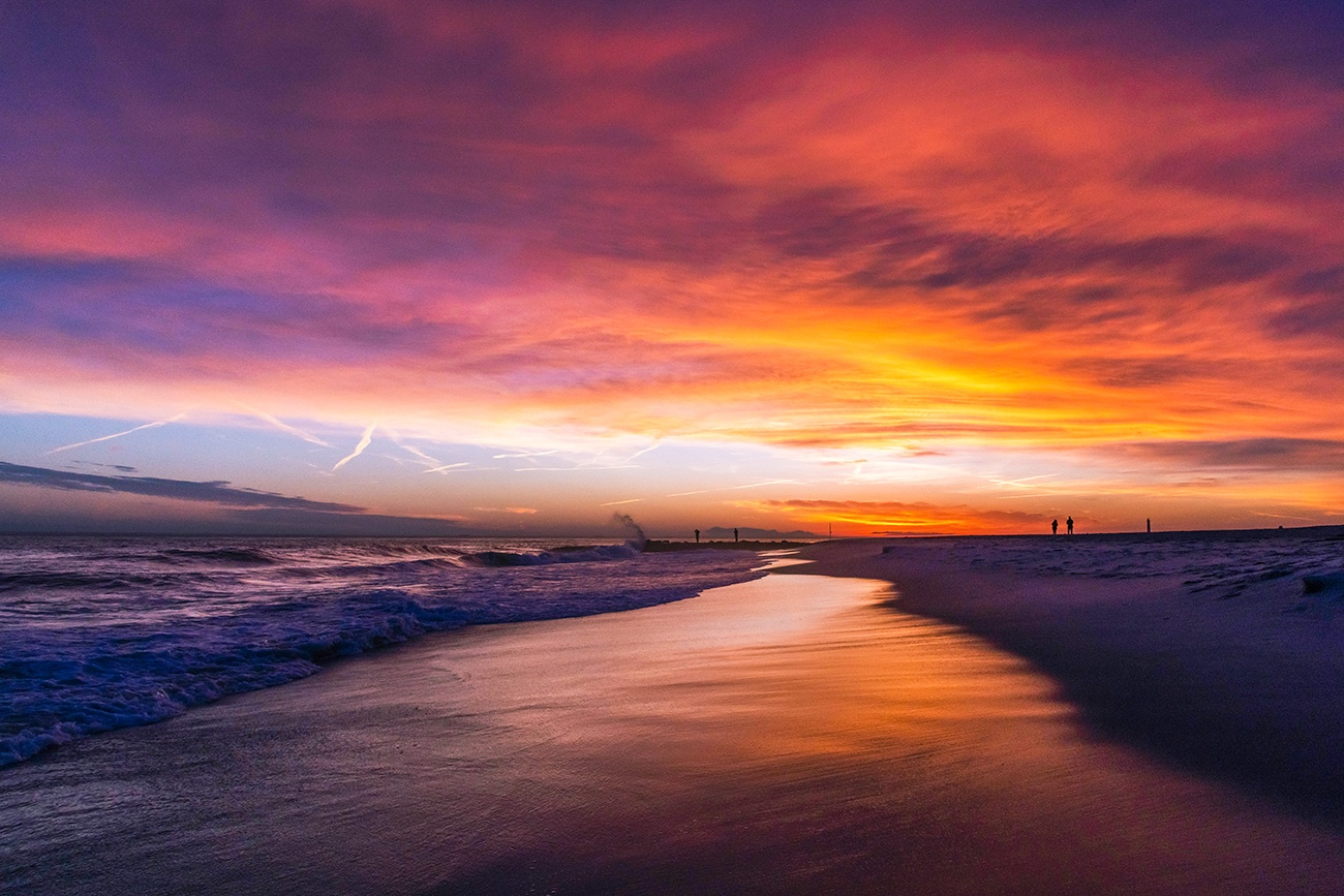 Colorful clouds in the sky at sunset by the ocean on the beach
