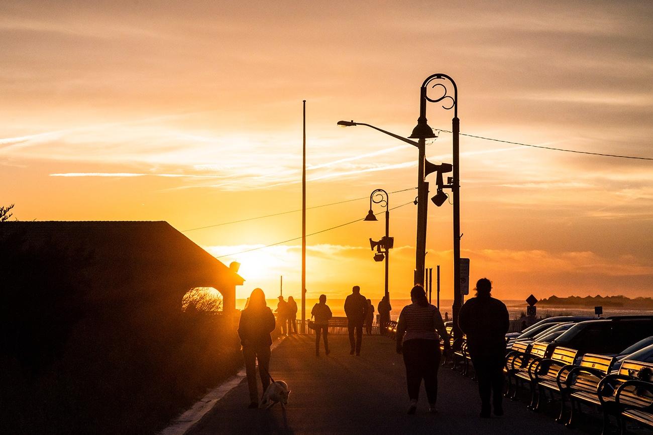 People walking on the promenade at sunset