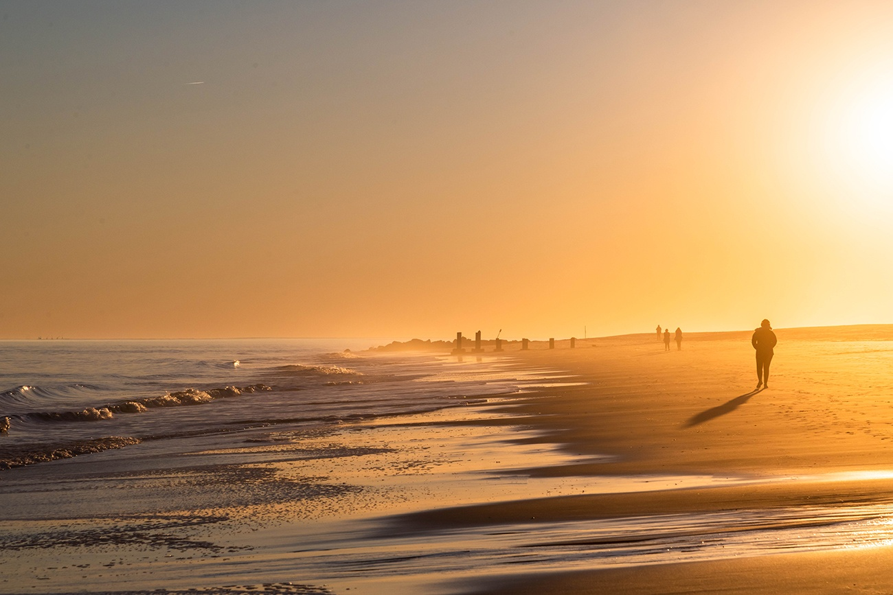 People walking on the beach at sunset