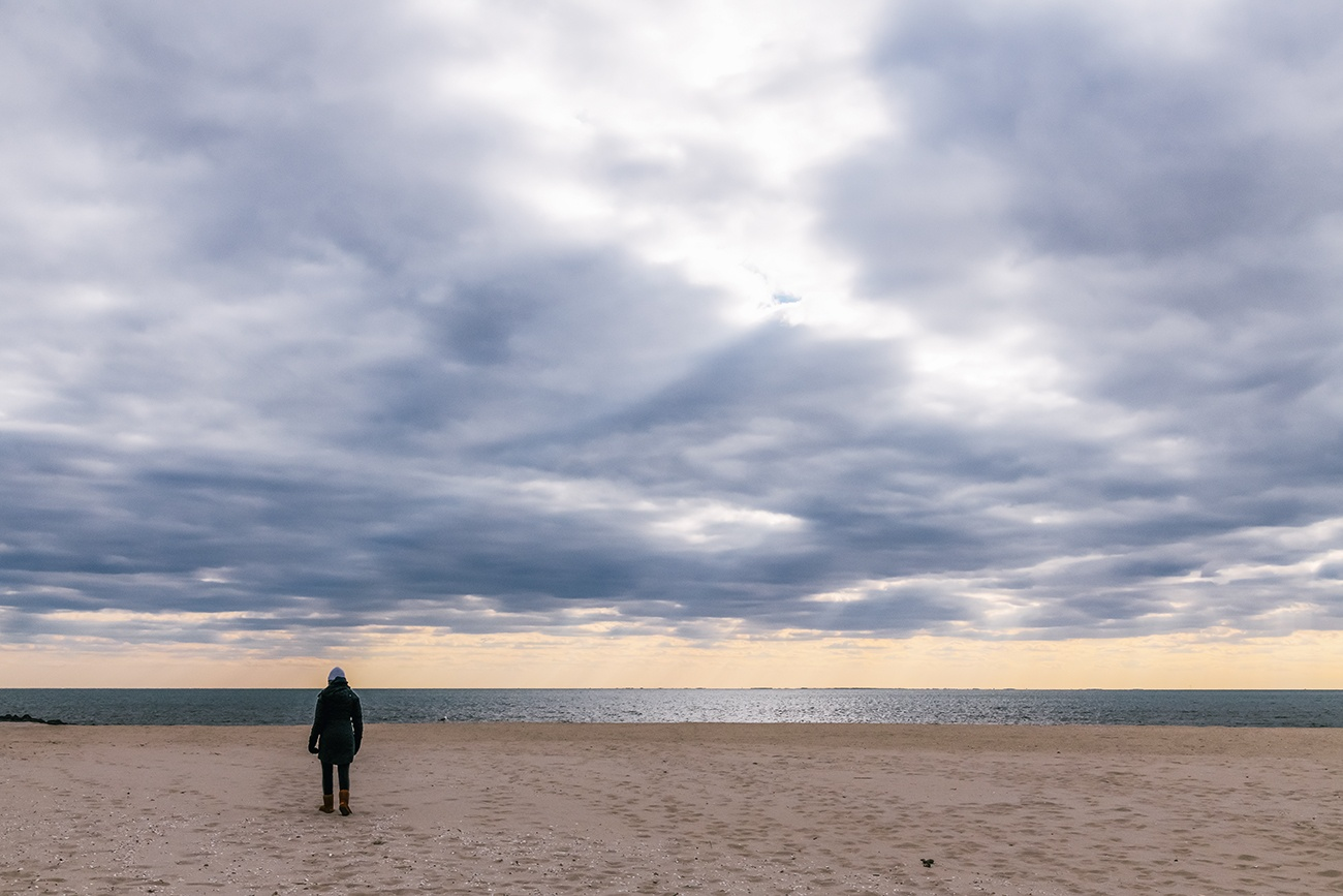 A person walking on the beach on a cloudy day