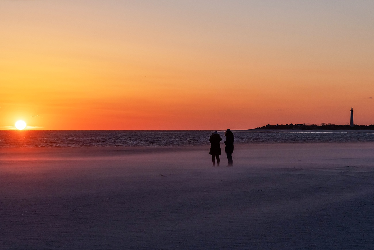 Two people watching the sun set at the beach in winter as the cold air blows sand