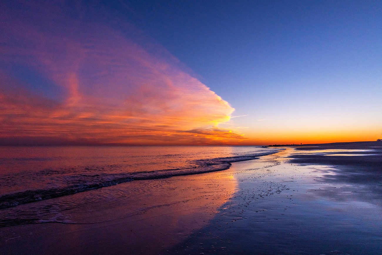 Colorful clouds in the sky at sunset reflected in the ocean and sand