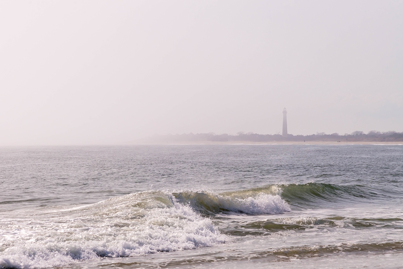 The Cape May Lighthouse in the distance on a foggy day with waves crashing