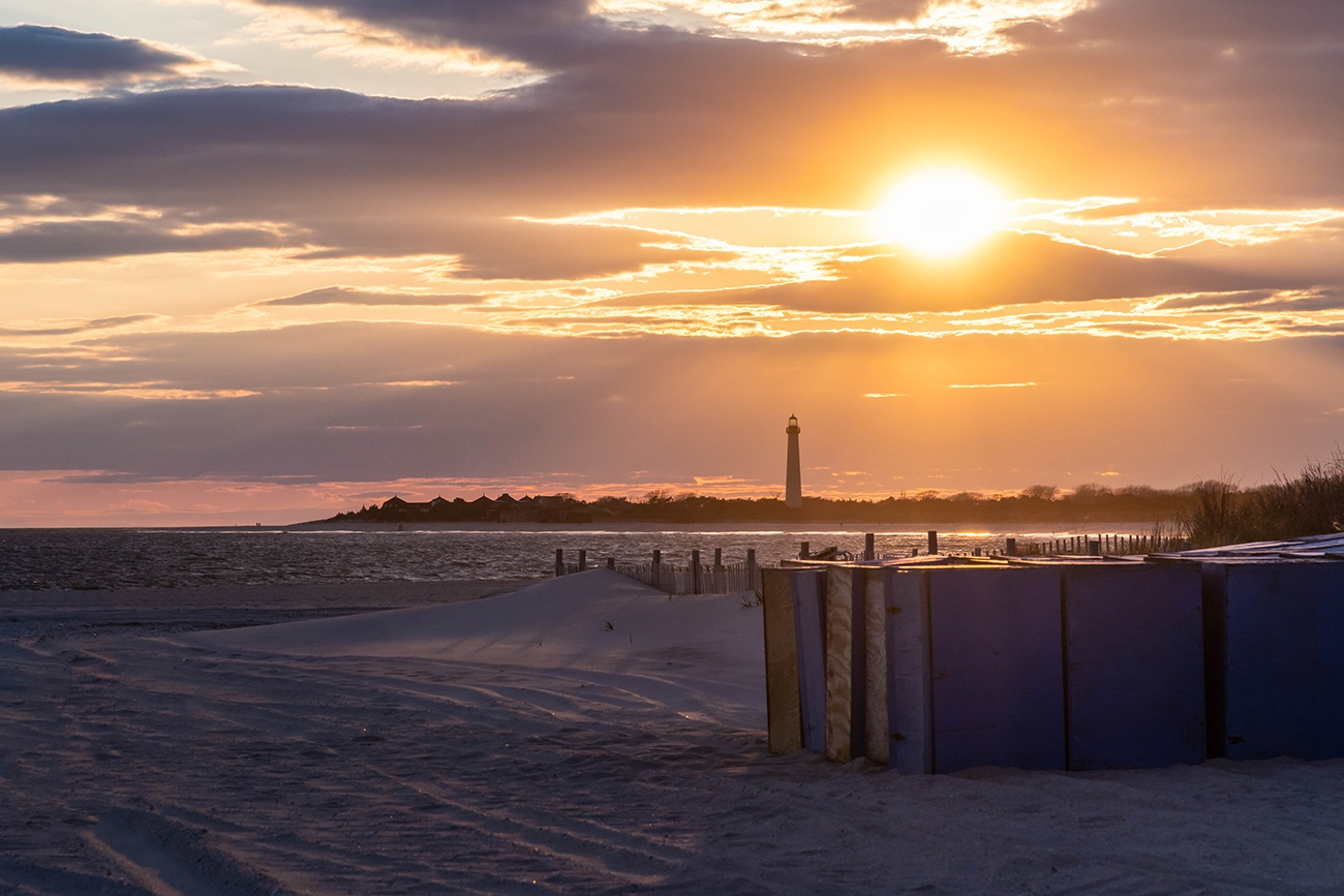 Sun setting behind the Cape May lighthouse with Steger's beach boxes on the beach