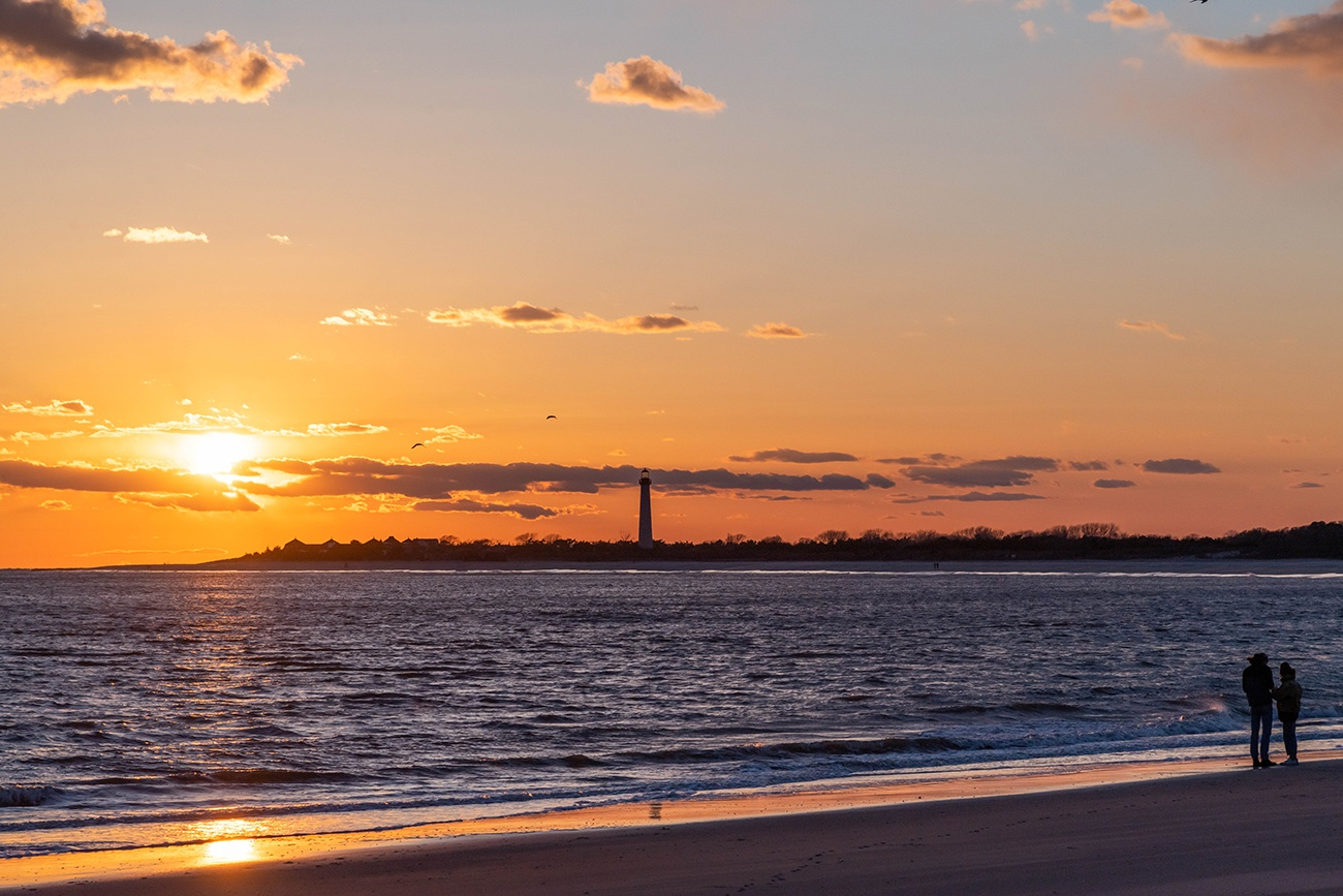 Two people watching the sun set with the Cape May Lighthouse in the distance
