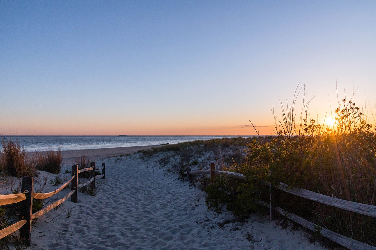 A path entrance to the beach with the sun setting
