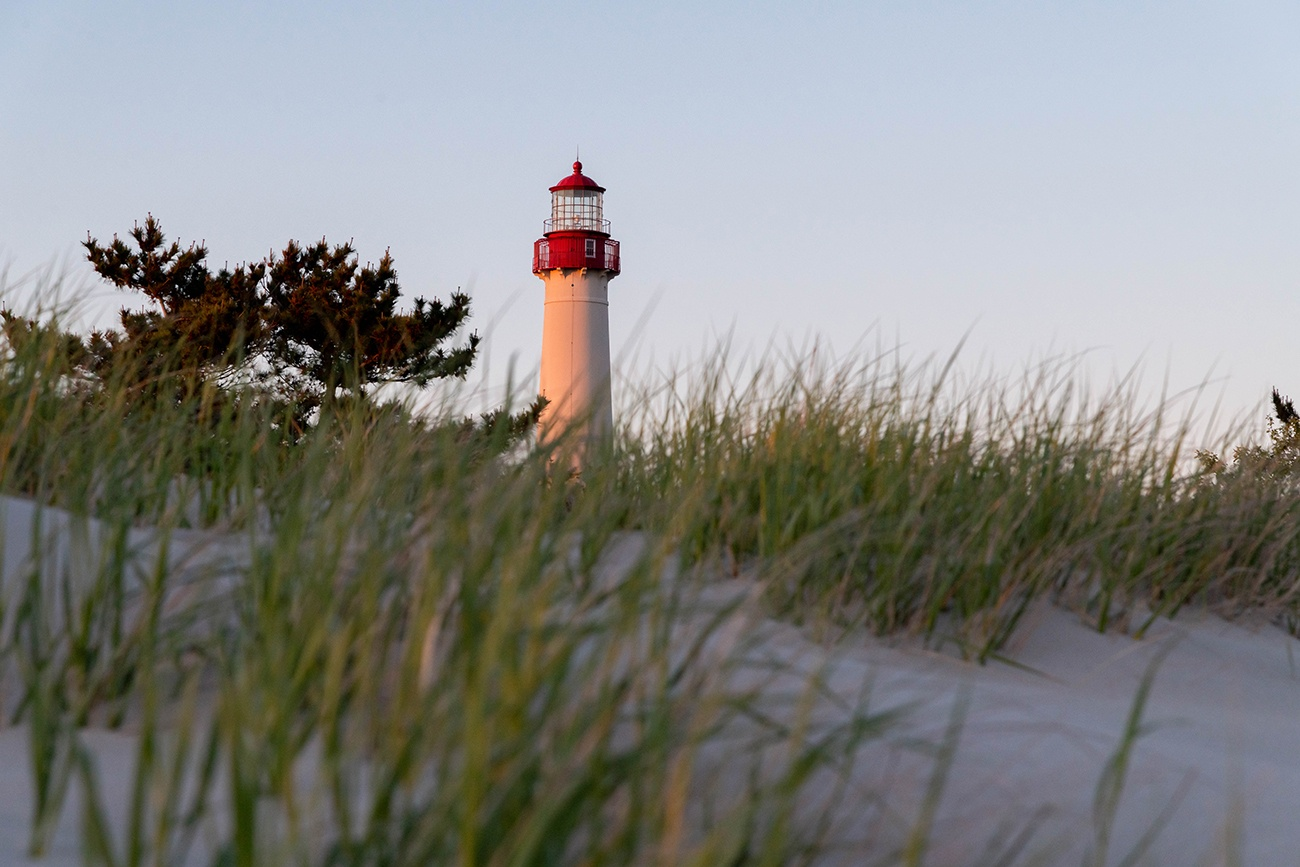 Sunlight on the Cape May Lighthouse with green beach dunes in the foreground