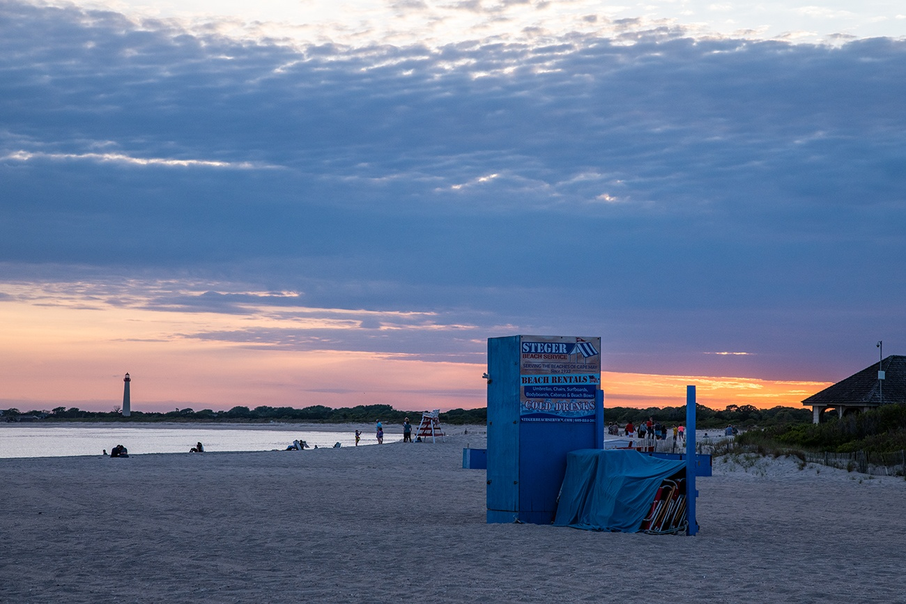 Steger's beach service box and chairs covered up at the end of the day at sunset with the Cape May Lighthouse in the distance