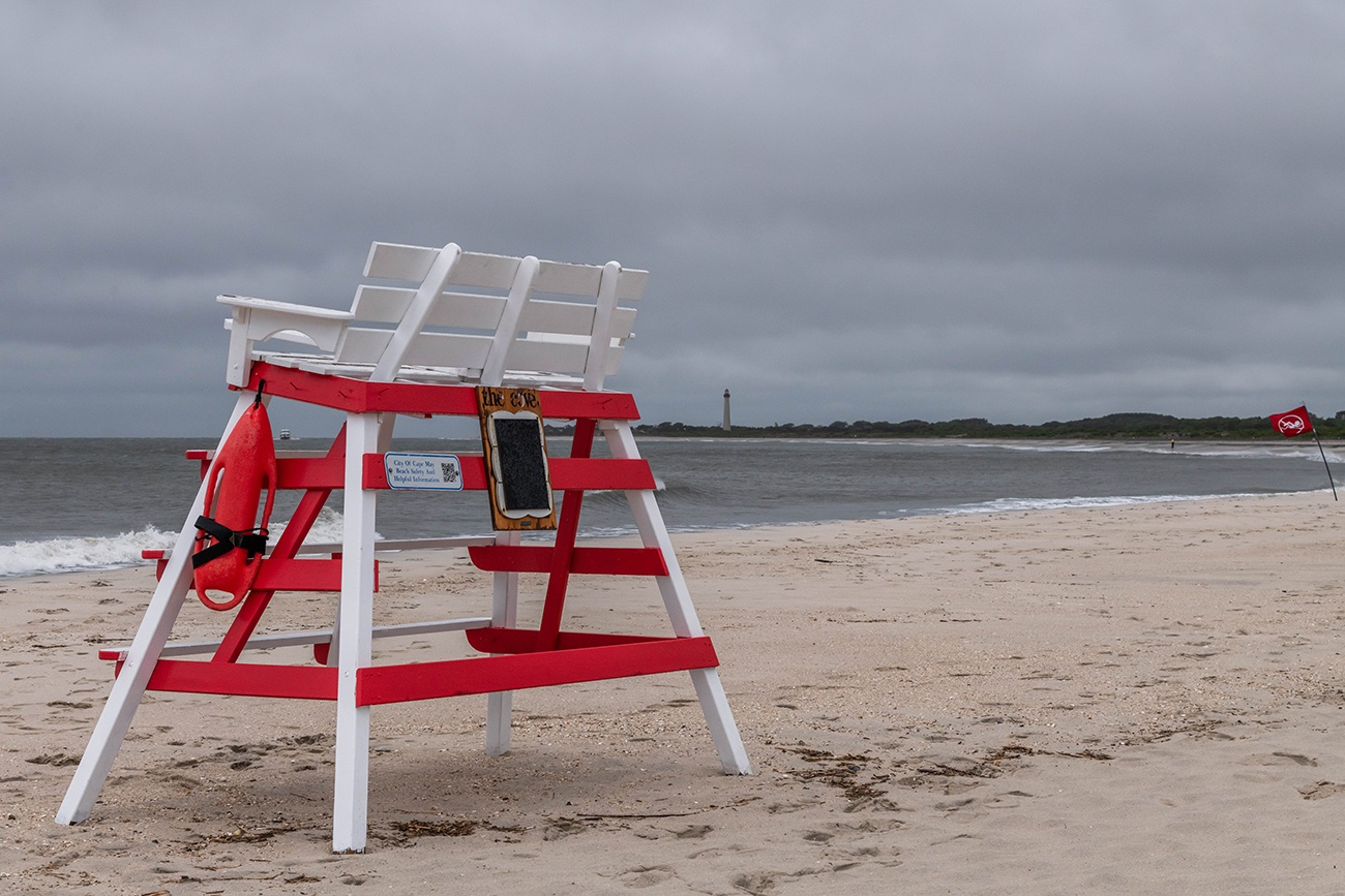An empty lifeguard stand at The Cove on a rainy and cloudy day with the Cape May Lighthouse in the distance