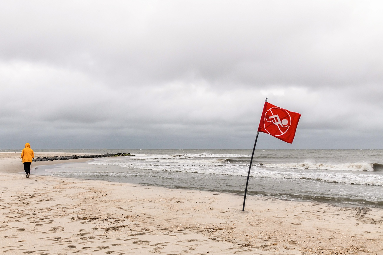 A person walking on the beach on a stormy cloudy day with waves crashing and a red no swimming sign on the sand