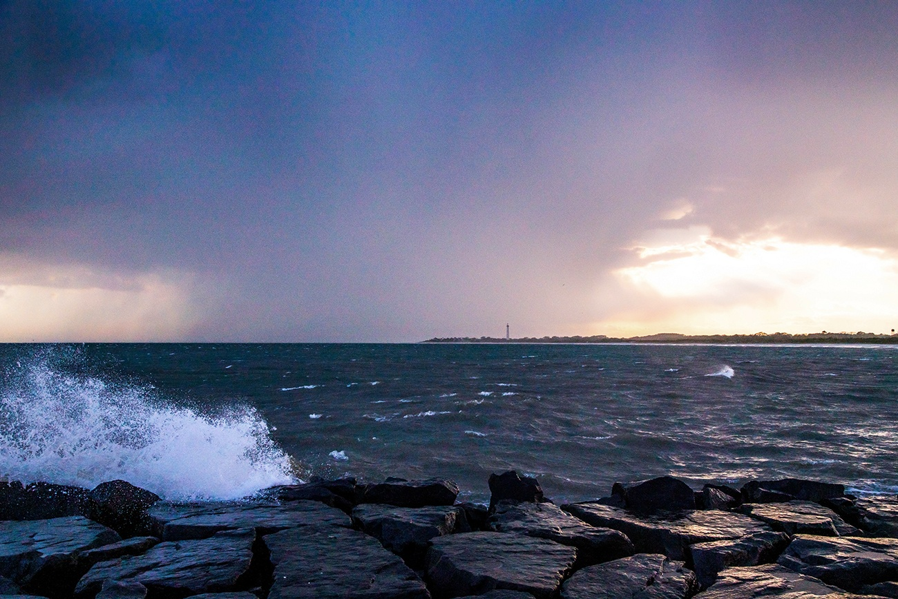 Rain storms at sunset with waves crashing and the Cape May Lighthouse in the distance