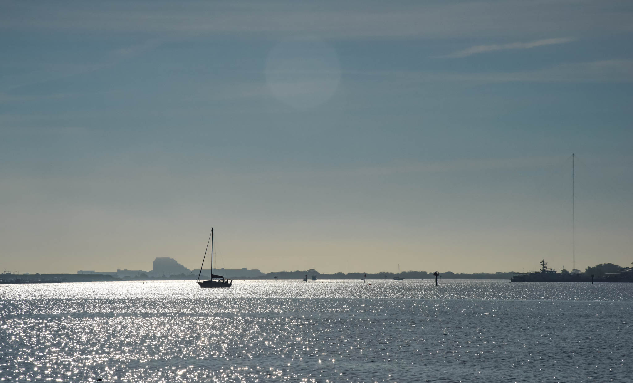 A sailboat sailing away in the Cape May Harbor in the early morning.