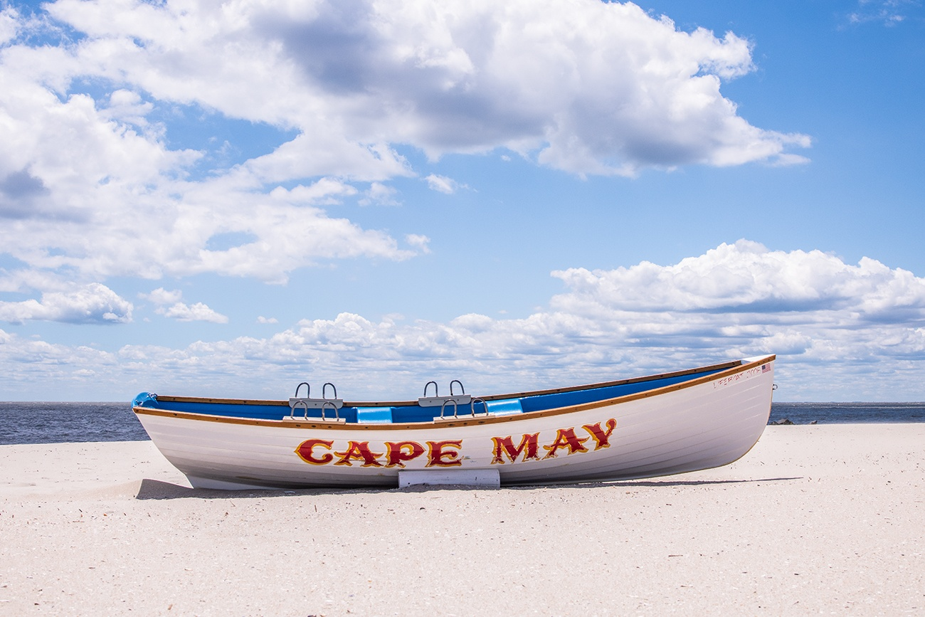 A Cape May lifeguard boat on the beach on a sunny day with blue skies and puffy white clouds