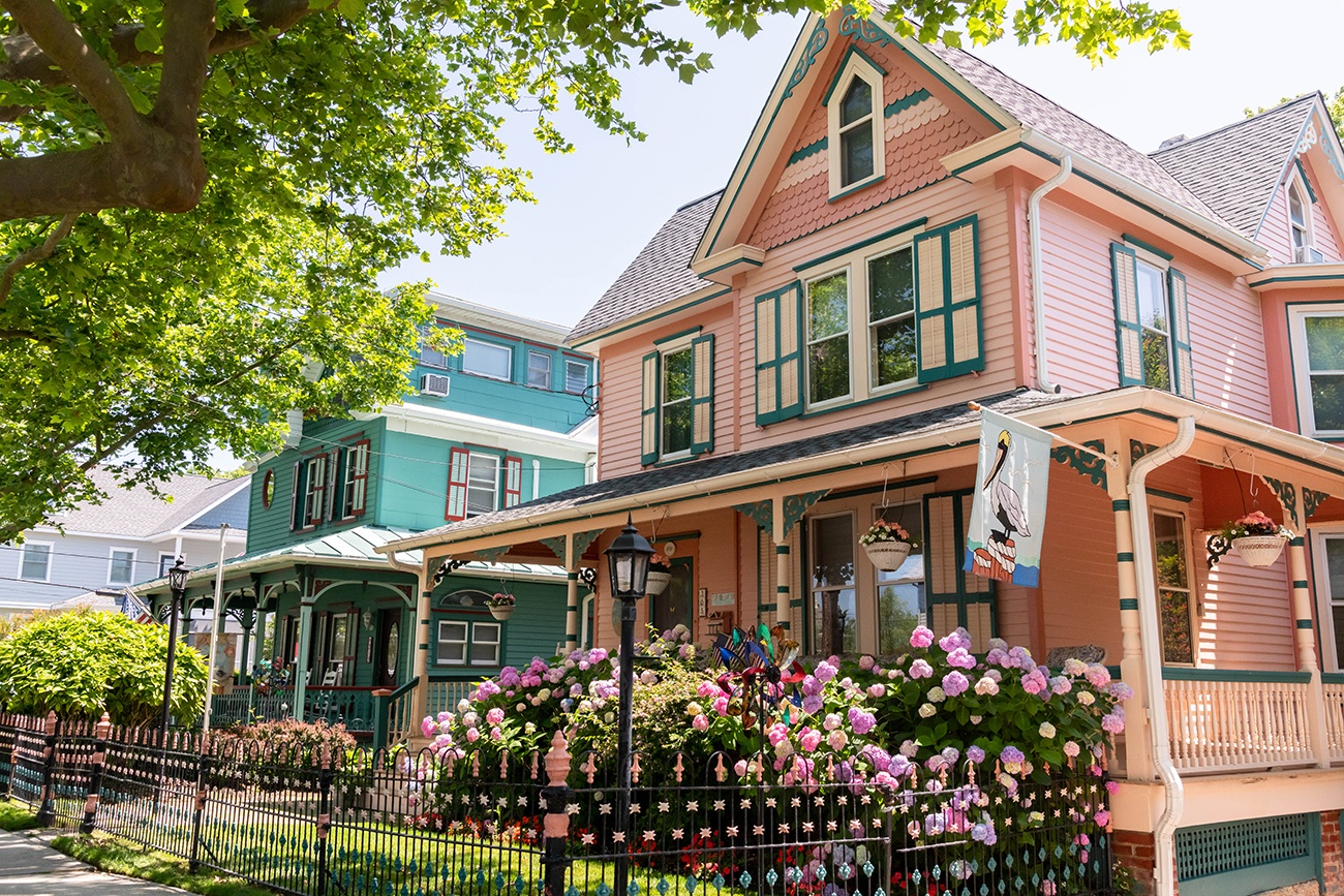 A pink Victorian house with pink and purple hydrangea on a sunny day