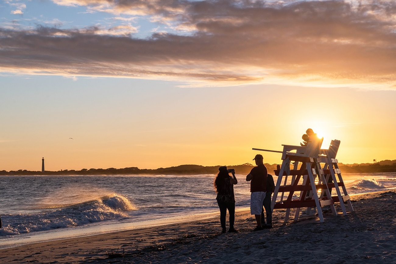 People sitting on lifeguard stands and standing by the ocean watching the sunset as waves crash along the shore