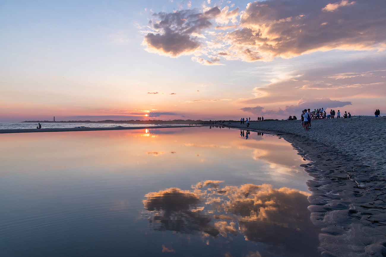 Sunset reflected in a pool of water at the beach with the Cape May lighthouse in the distance