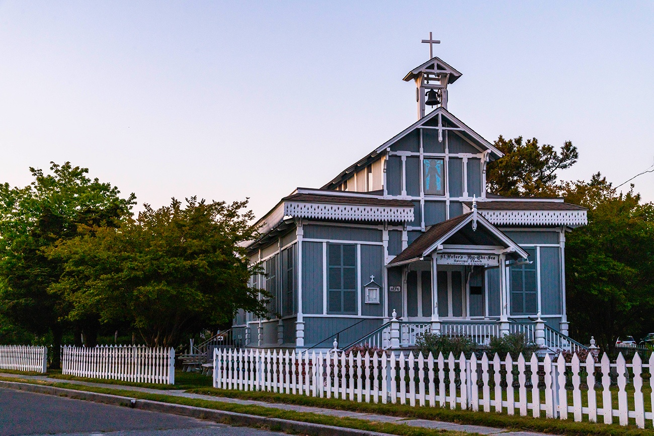 St. Peter's by the Sea, a small teal church with a white fence, at dusk