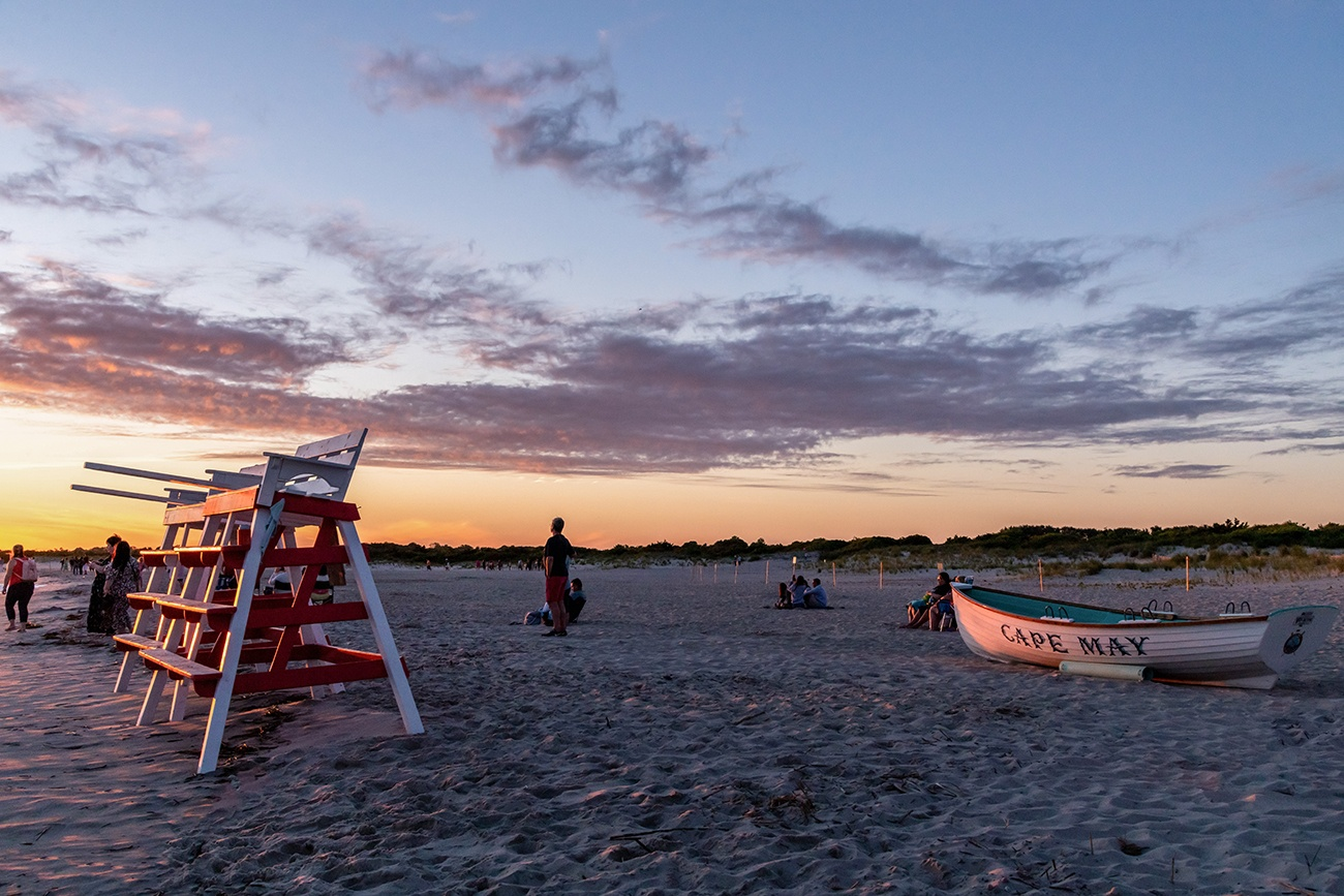 Two lifeguard stands and a Cape May boat shining in sunset light on the beach
